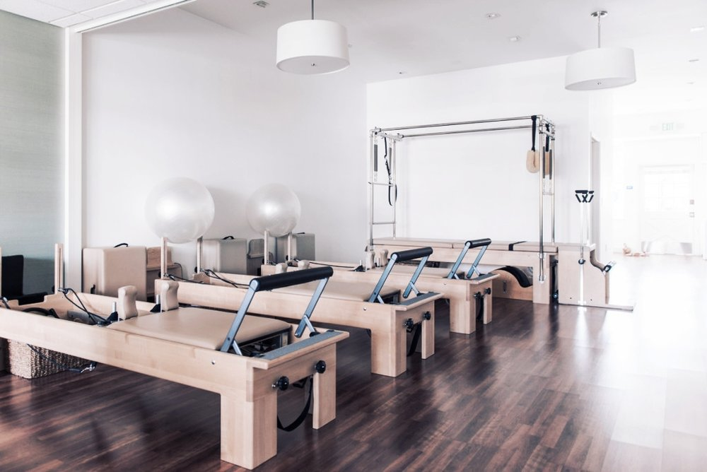 An attractive studio filled with natural light for private and small group classes, visible within but separate from the overall space. Women will be more likely to take care of themselves because of its convenience and the power of seeing other mothers who are taking time to focus on their health and wellness.