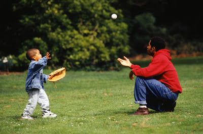 Father and son (3-4) playing catch in park, side view