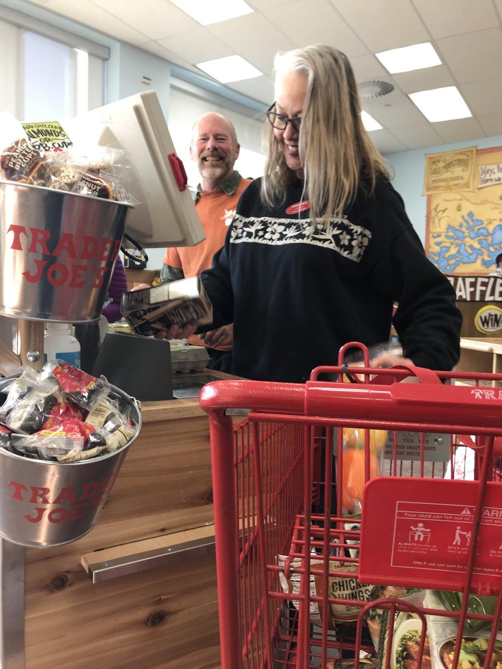 A man and woman cashier at Trader Joe's emptying cart.
