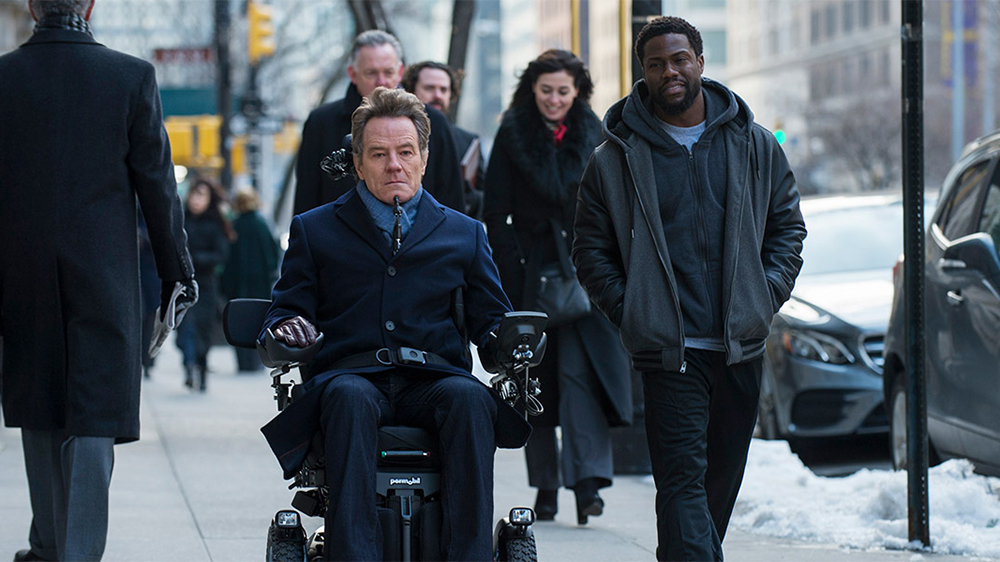 "Film still shot with Bryan Cranston in a power wheelchair alongside Kevin Hart for the film ""The Upside"""