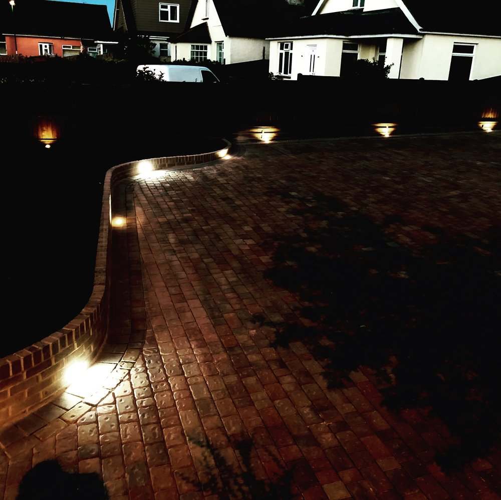 Using driveway lighting as well as lights within the brick wall creating a stunning and welcoming driveway at night, installed in Bognor Regis West Sussex.