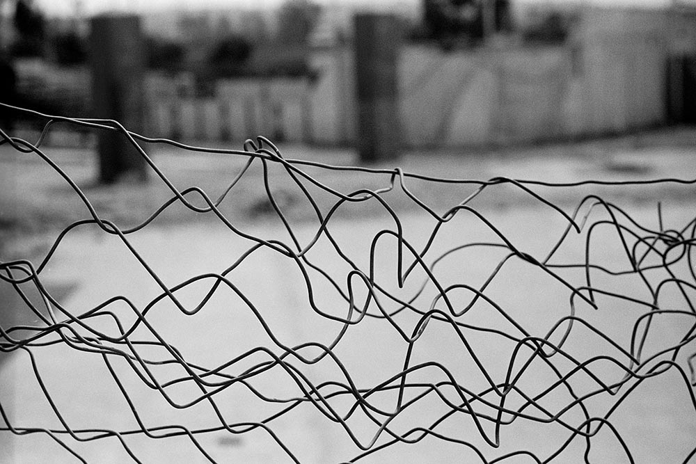 Black and white photo of a twisted wire fence.