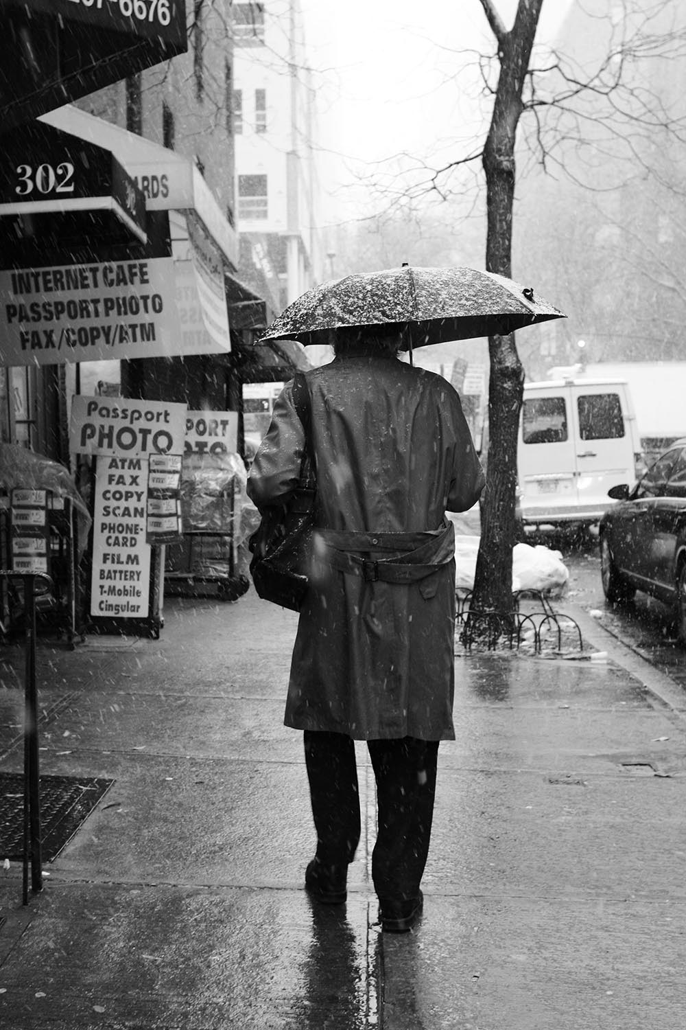 Black and white photo of a drenched man in a trenchcoat walking in the snow.