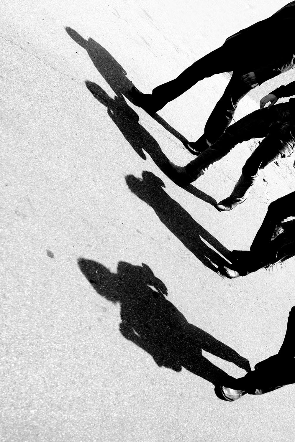Black and white photograph of four men casting shadows on the street while walking.