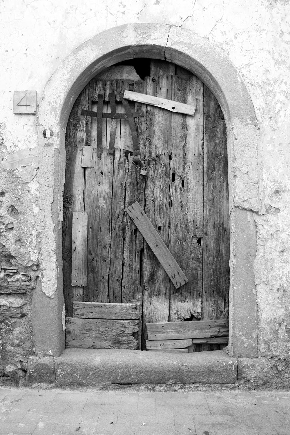 Black and white photo of an old wooden door nailed shut with plywood.