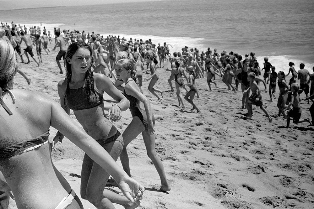 Black and white photo of a beach covered in running, screaming children.