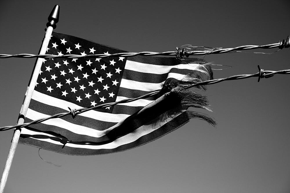 Black and white photo of an American flag being ripped apart by barbed wire.