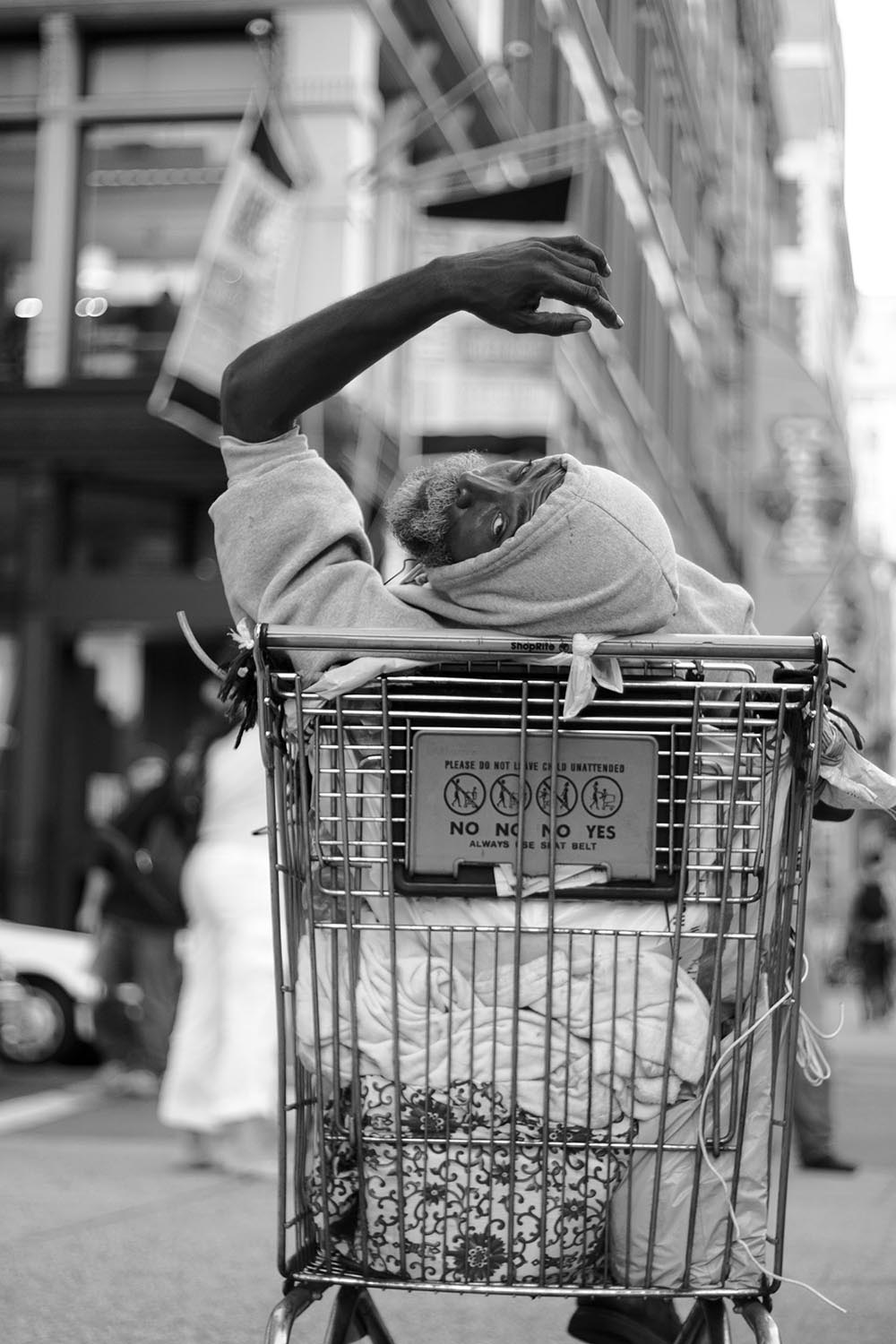 Black and white photograph of a homeless man in New York City resting himself inside a shopping cart.