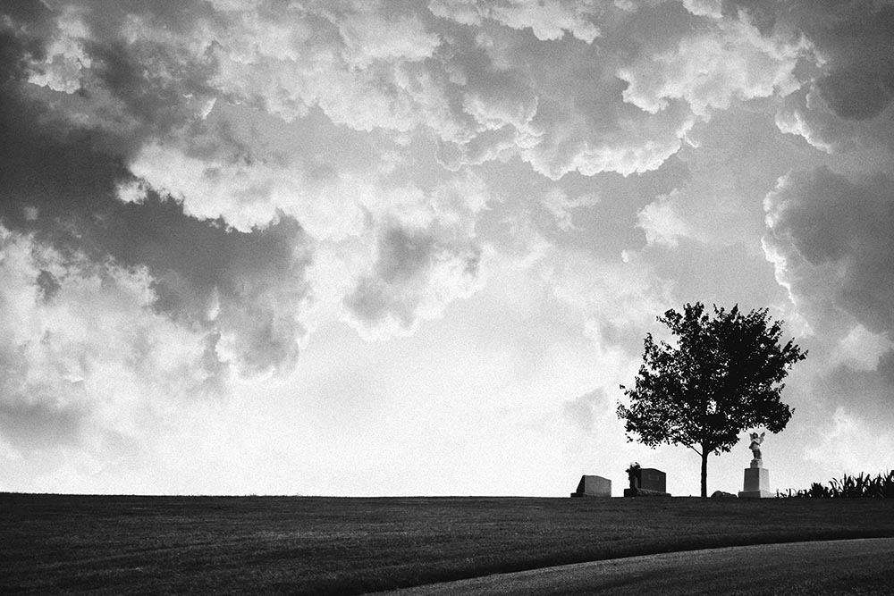 Black and white photo of a small cemetery on a country hillside.