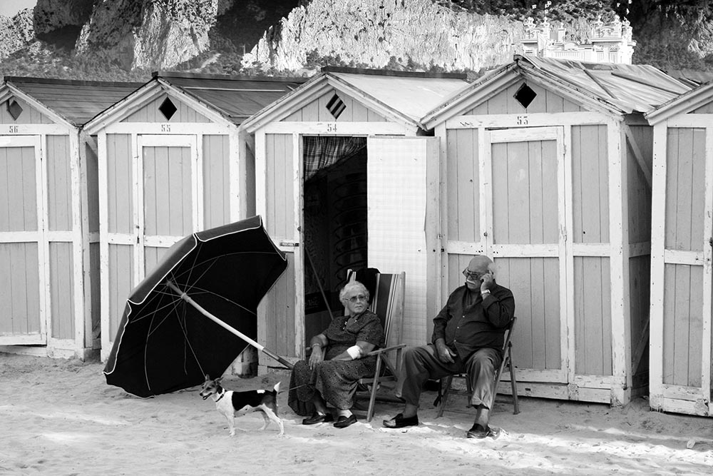 Black and white photograph of an elderly couple and their dog on a Sicilian beach.