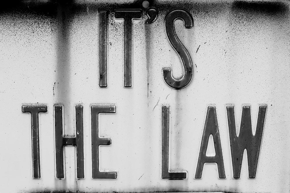"""Black and white photo of a rusted sign that says """"It's the Law."""""""