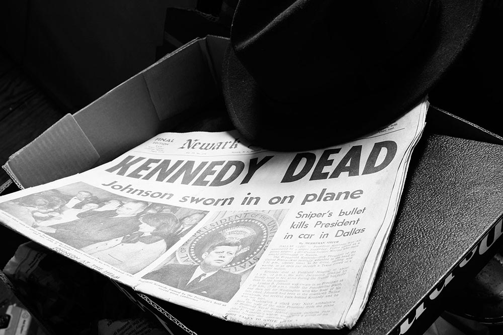 """Black and white photograph of a newspaper with the headline """"Kennedy Dead."""""""