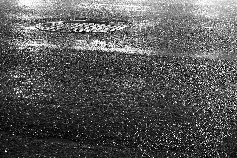 Black and white photo of a manhole cover lit by traffic lights.