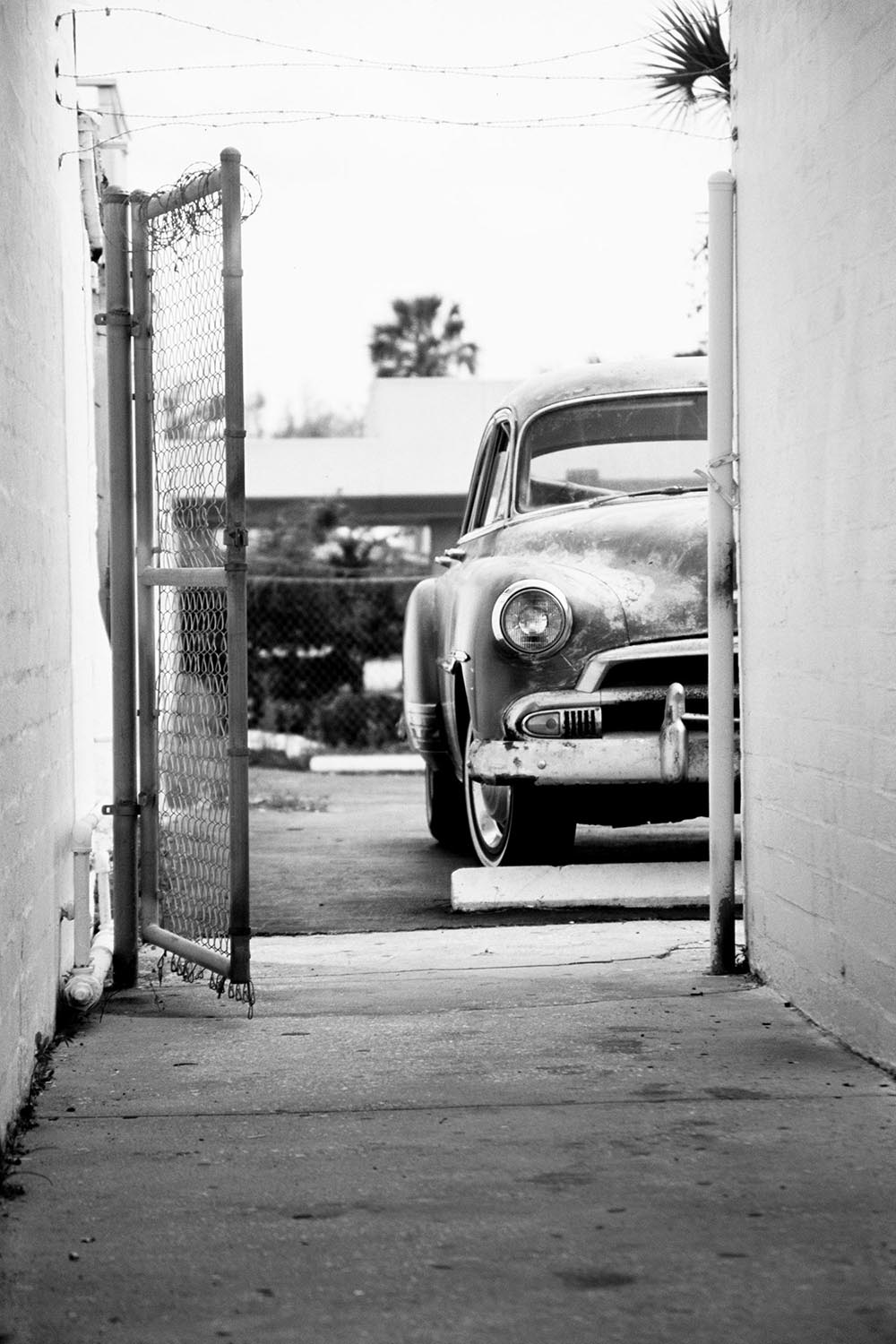 Black and white photograph of an antique car half-seen down an alley way.