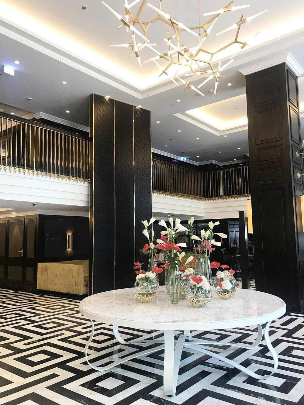 The hotel lobby has a beautiful floor tile design.