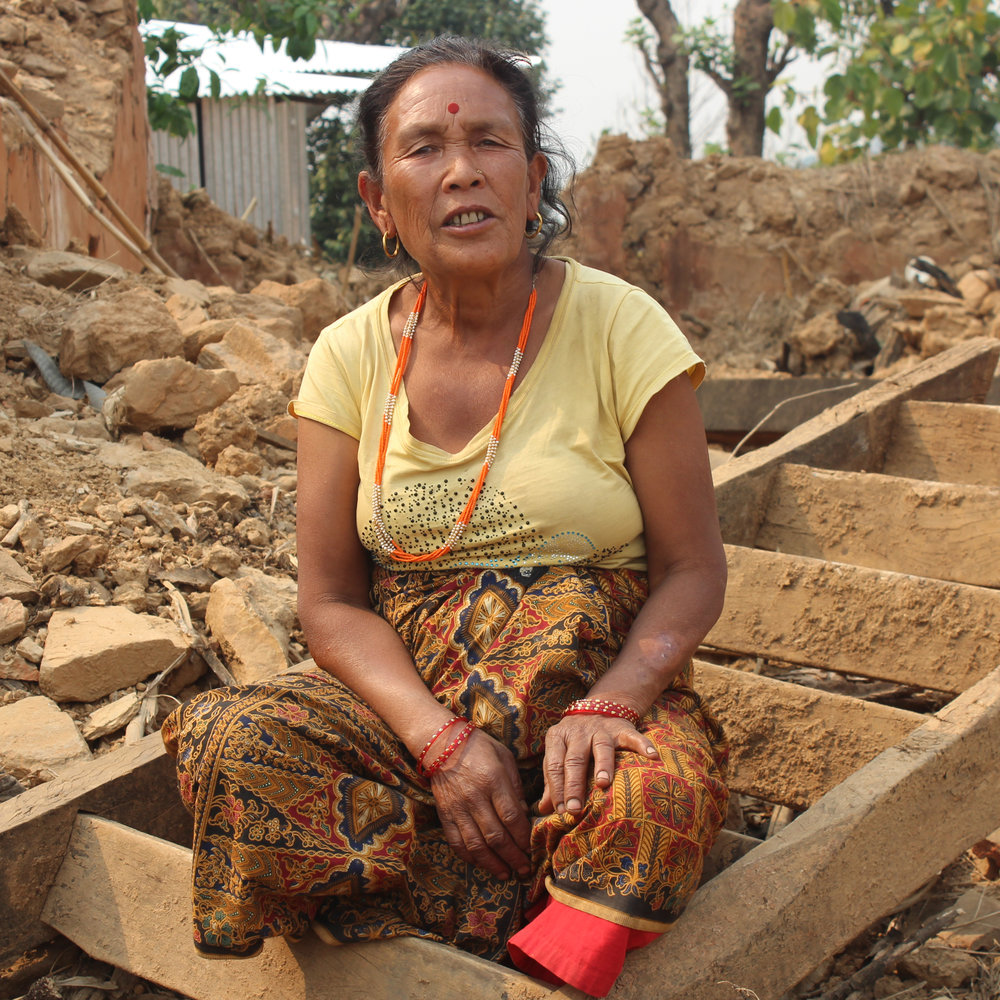 Kanchi Tamang, 60, amid the ruins of her house.