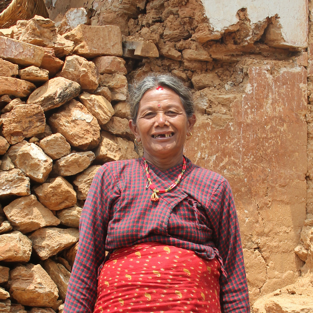 Manumaya Pahari, 62, all smiles in front of her former home.