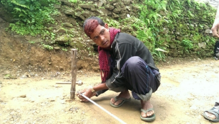 A local construction worker measures the layout for a foundation in Rainaskot