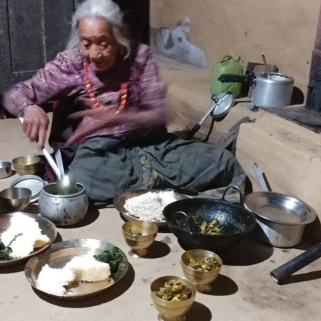 "One of our Aamas (or Moms) in Rainaskot dishes up a dinner of rice and dal, otherwise known as ""dal bhat"", the national dish of Nepal.  Most Nepalis agree that they haven't eaten if they haven't had rice twice a day."