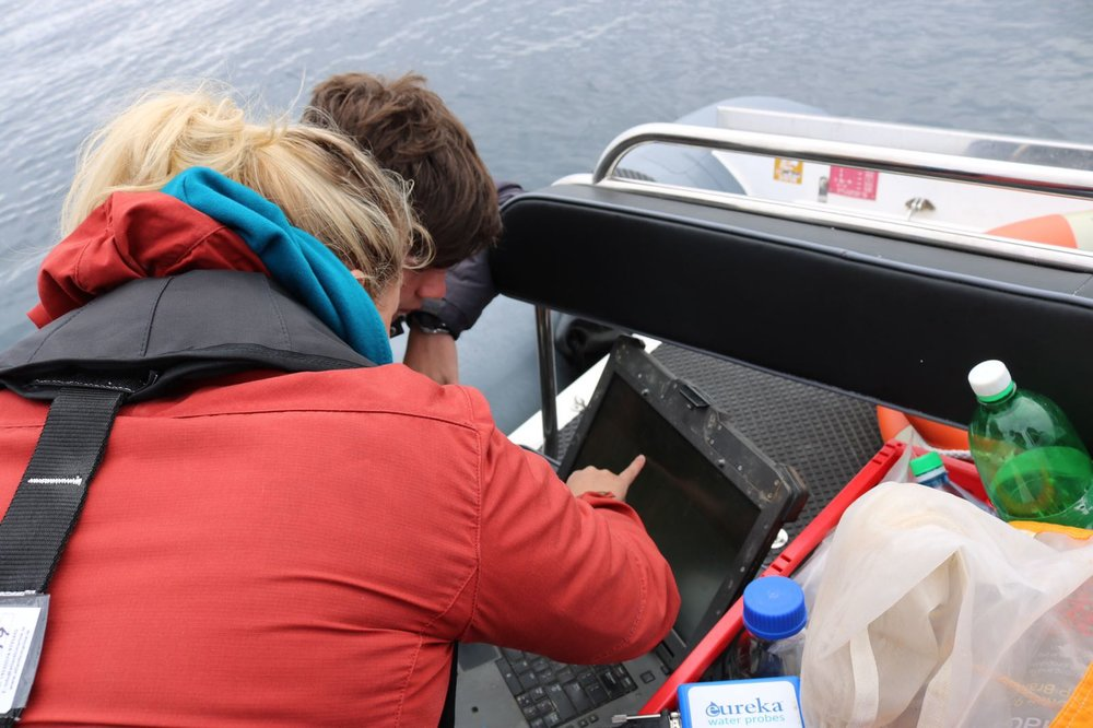 Heather shows a Coastal Explorer how to take a snapshot sample of the water column, using an environmental probe that measures temperature, depth, salinity, dissolved oxygen, and pH.   Photo by:  Chelsea Gray