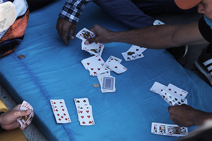 "Playing cards outside Benito Juarez stadium complex. Zona Norte, Tijuana. November, 2018.    Central American migrants pass the time outside the stadium complex in Tijuana's ""North District"" where currently 4,500 migrants are currently housed under tents and tarps. Helicopters fly overhead 24 hours a day. The border lies less than 100 feet."