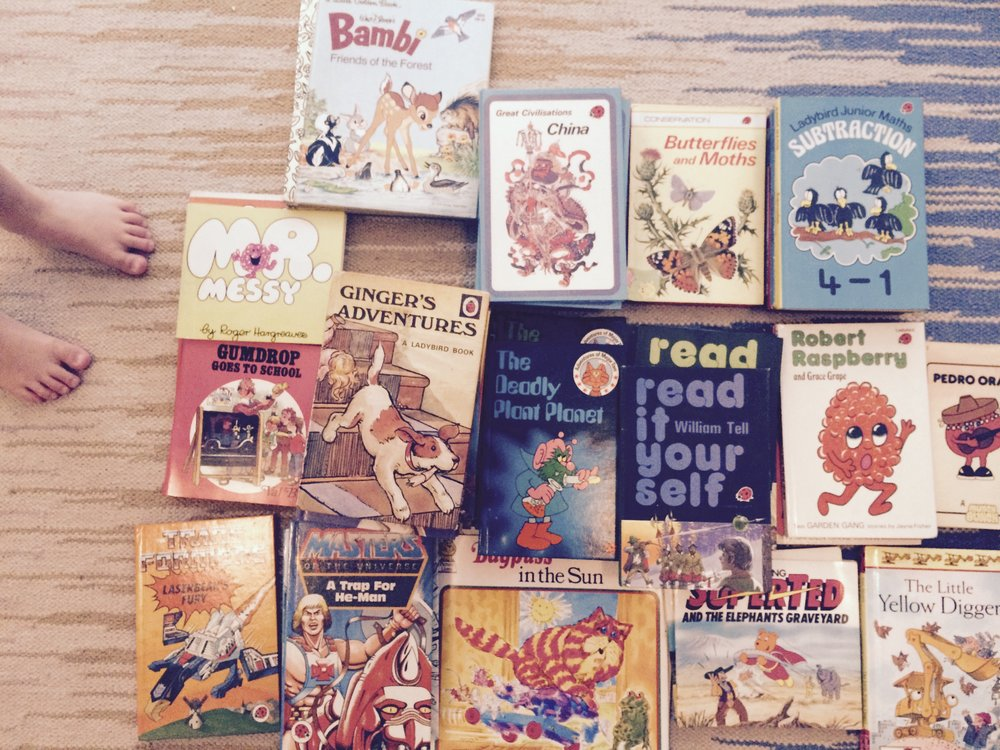 a selection of children's books spread out on a rug.JPG