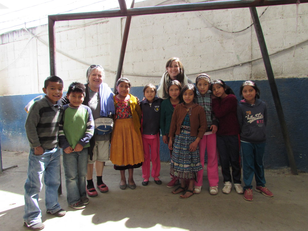 Kids from the public school in Concepcion Chiquirichapa, Guatemala pose for a photo with Patricia Rebolledo and Emily Elizabeth Hill during the February 2017 Educational Tour.
