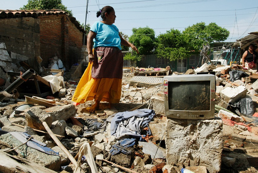 Chiapas, Mexico - A woman stands in the remnants of her house after a 8.1-magnitude earthquake struck close to the Pacific coast of Mexico. Credit: Reuters