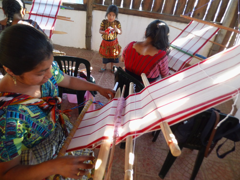 Indigenous women learn to weave textiles using a backstrap loom at AFEDES' Weaving School in Sacatapéquez, Guatemala.