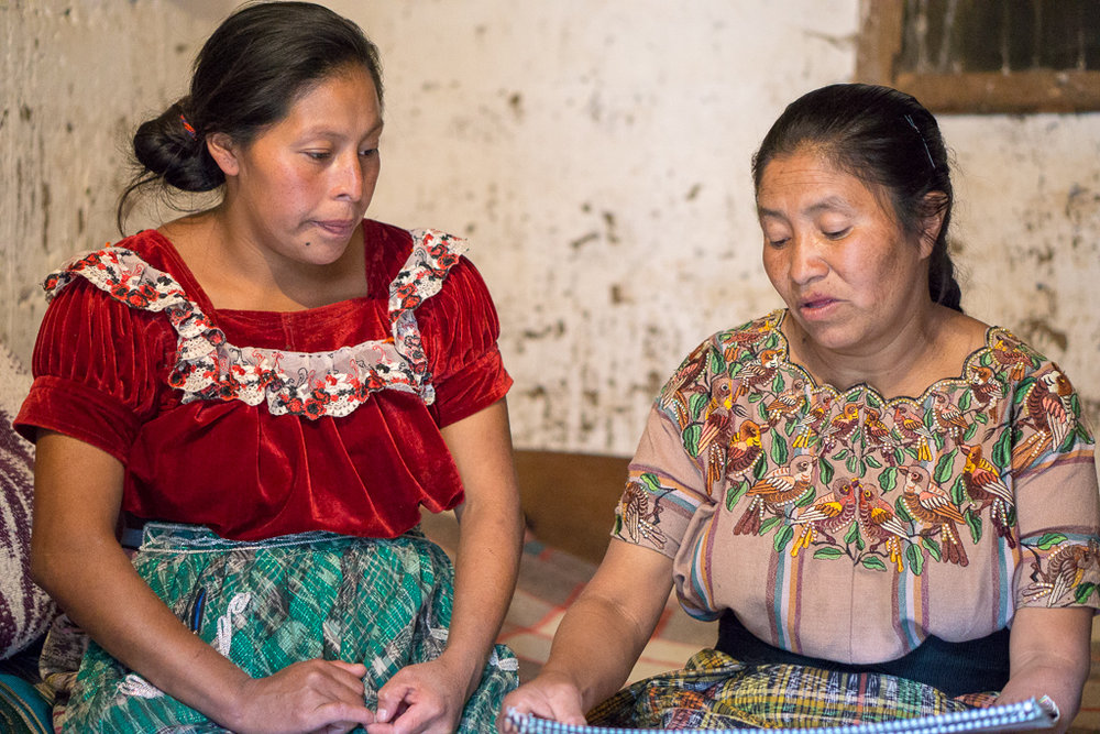 A traditional Maya K'iche' midwife teaches a pregnant woman about the warning signs of a high-risk pregnancy during one of her household visits.