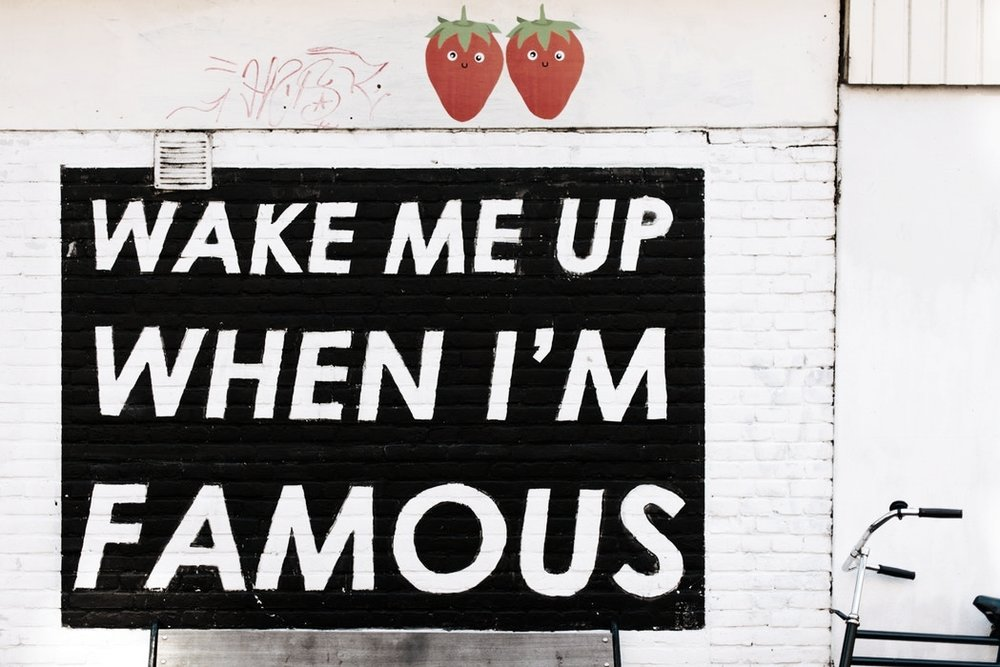 "Image description: Black square painted on a wall with the words ""Wake me up when I'm famous"" in big white letters."