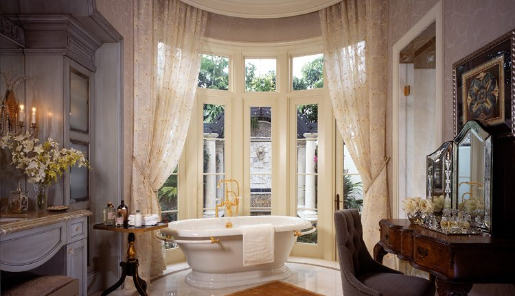 The elegant, feminine master bathroom includes a crystal chandelier and sconces.