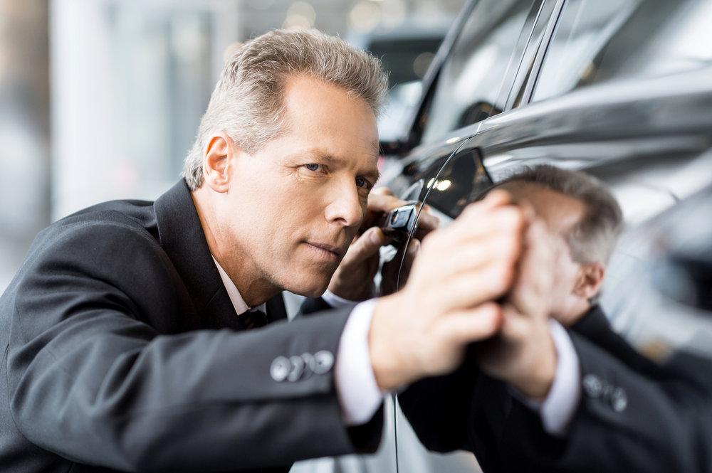 man-examining-black-car-with-eyes-and-hands.jpg