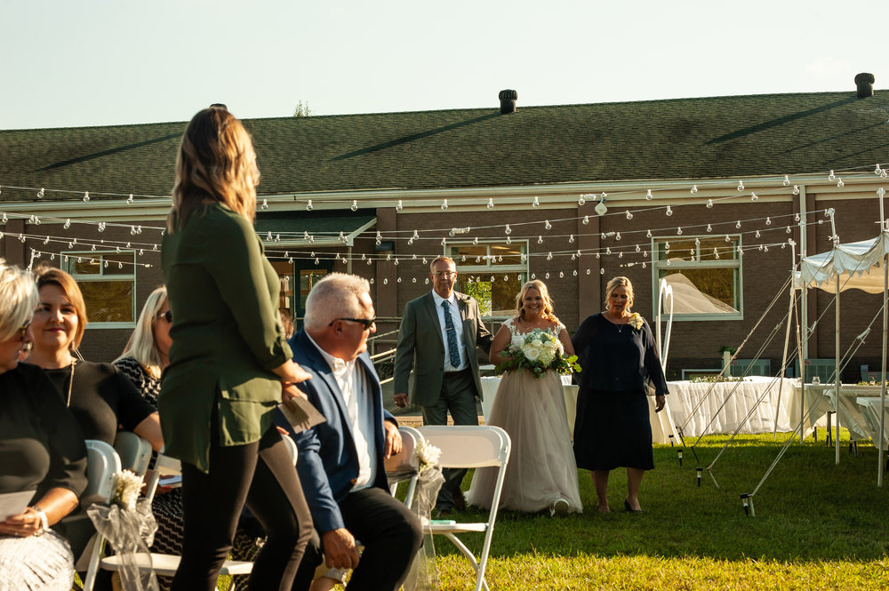 Sidney being walked down the aisle by her parents