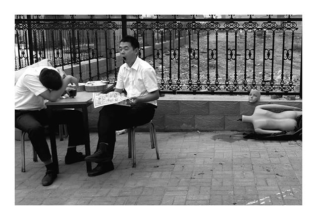 I photographed these two, and the mannequin, during the lunch break on a lazy, polluted, and gloomy afternoon in Shijiazhuang, Hebei Province, North China, 2015 © Arek Rataj  #china #asian #surreal #wtfisgoingon #blackandwhite #streetleaks #instastreet #triangular #yawn #portrait #tired #lunch #streetfood #sleepy #headless #pollution #streetphotos #streetphotography #traveler