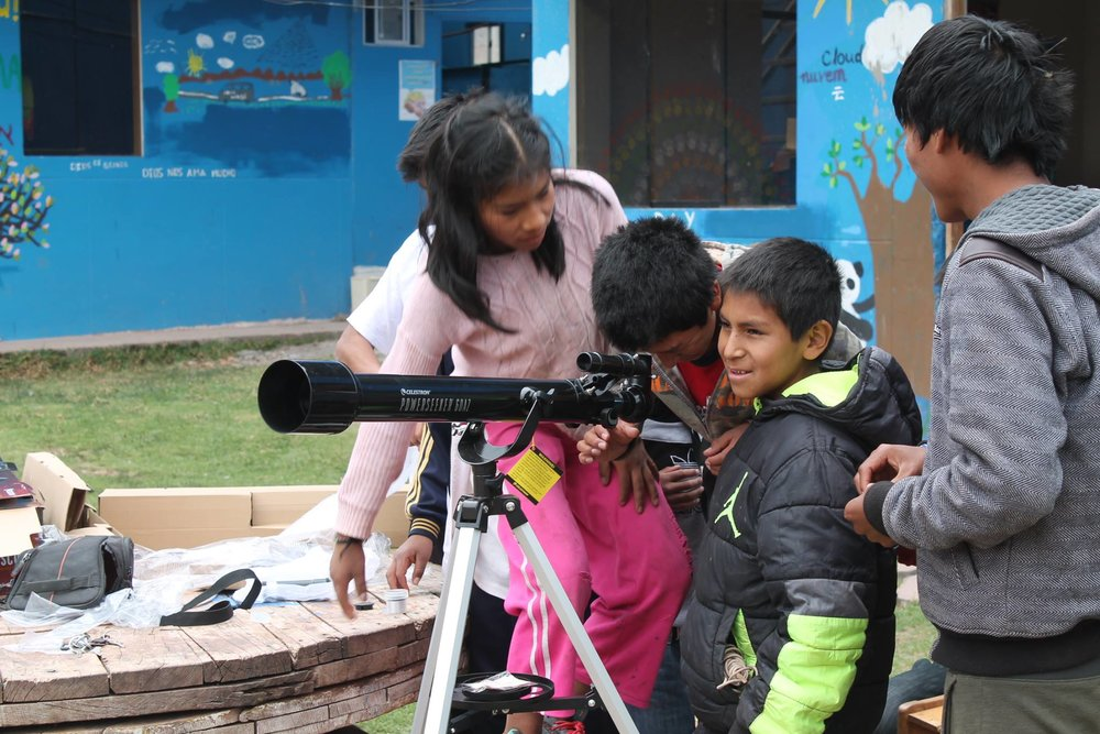 孤儿院的孩子们正在研究如何使用天文望远镜。