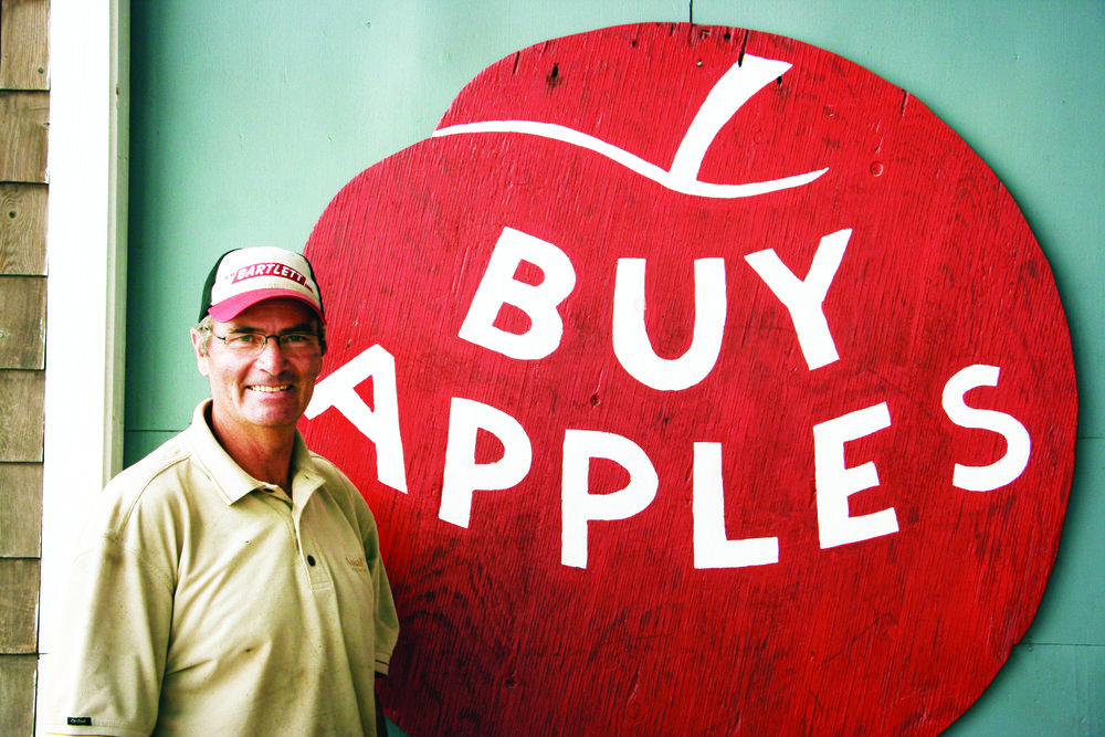 Blair Stirling with a sign featuring the Stirling apple brand designed by his father Robert. (George Fullerton photos)