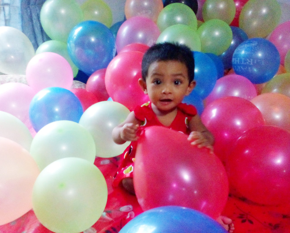 One_year_baby_is_playing_with_birthday_balloons.jpg