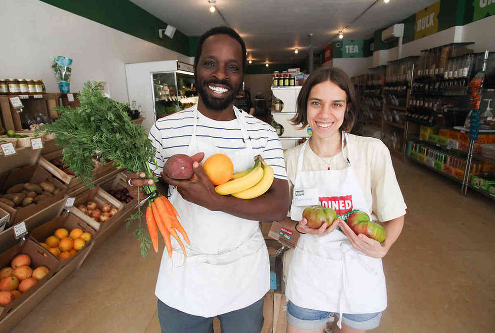 Co-op member-owners Calixte and Mariana show off fresh produce. Photo courtesy of Brooklyn Paper.