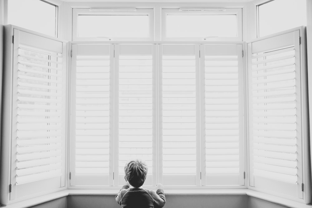 Boy looking out of window on a rainy afternoon Kirsty Hamilton Photography