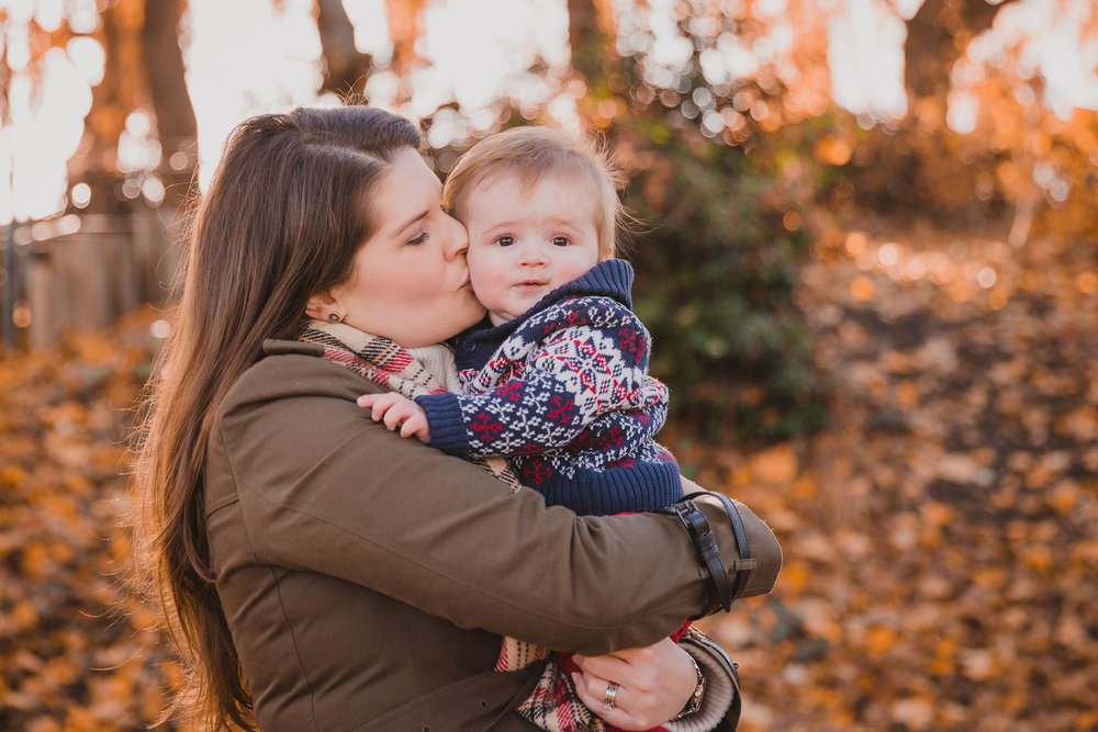 Mum cuddles sweet baby boy in autumn leaves