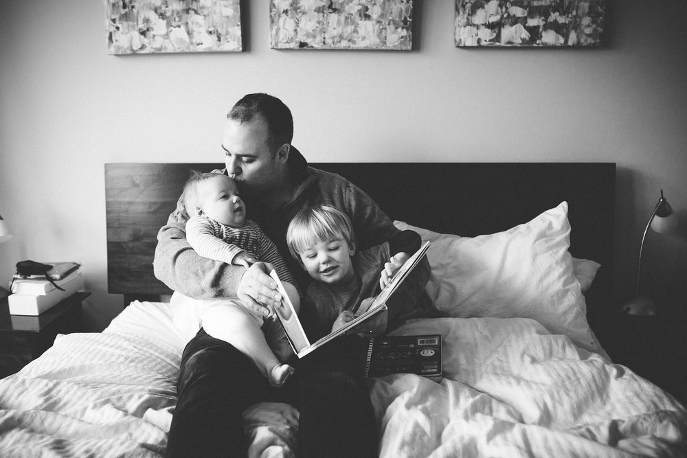 Dad cuddles baby boys reading a story, London Family Photography