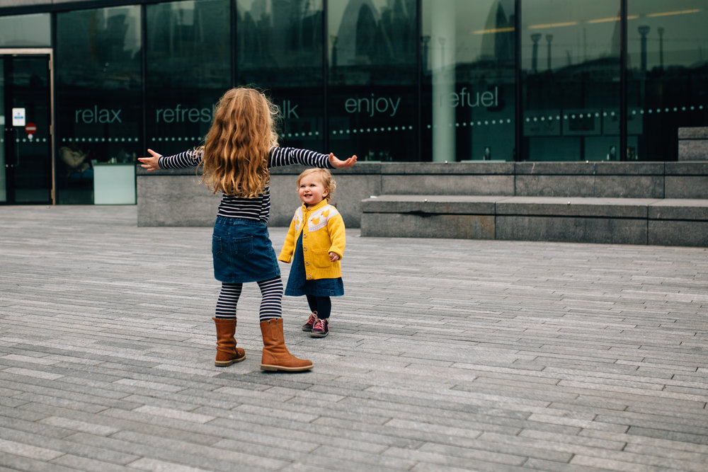 Sisters play outside City Hall, London, Tower Bridge Family Photographer