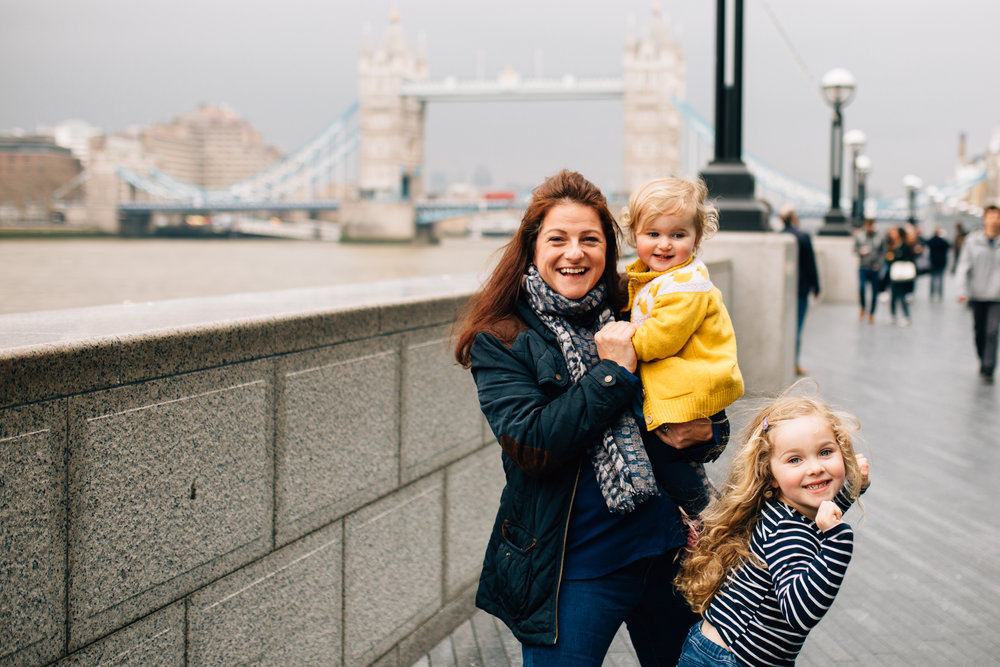 Mum dances with girls at family photography session at Tower Bridge London