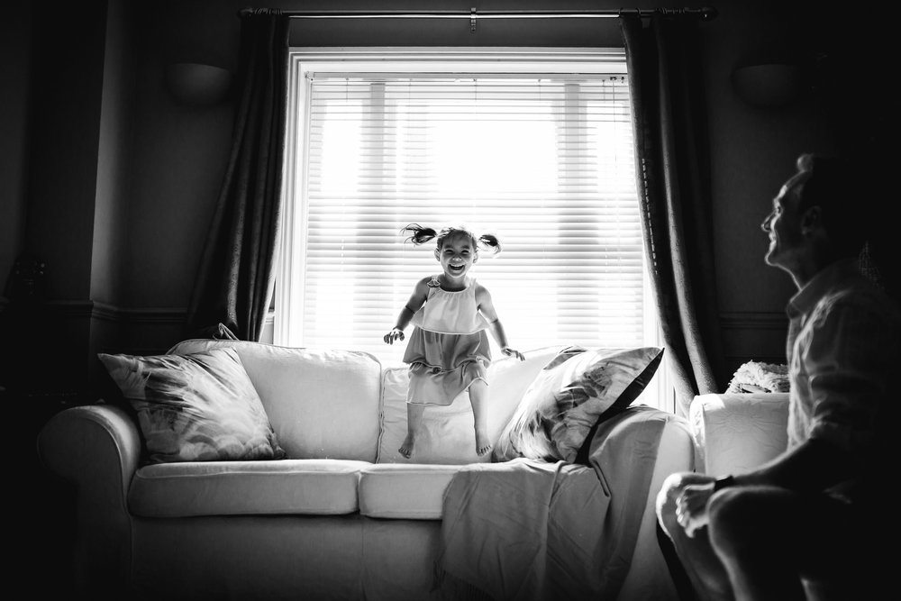 Little girl jumping on sofa - family photographer
