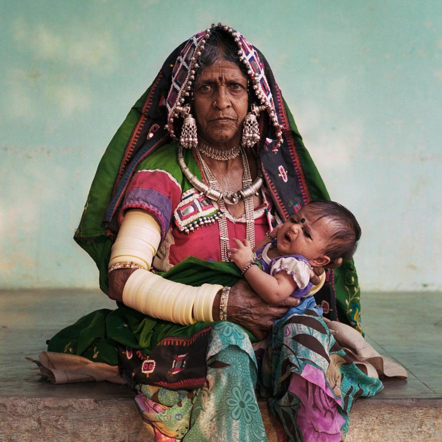 "One of Yadav Bhavanth's relatives, Biki Malavath holds her great-granddaughter, nicknamed Milky, the youngest member of Laxmapur Thanda. The village is home to the Lambadi people, a ""scheduled tribe""—defined as one of India's marginalized and socioeconomically disadvantaged communities."