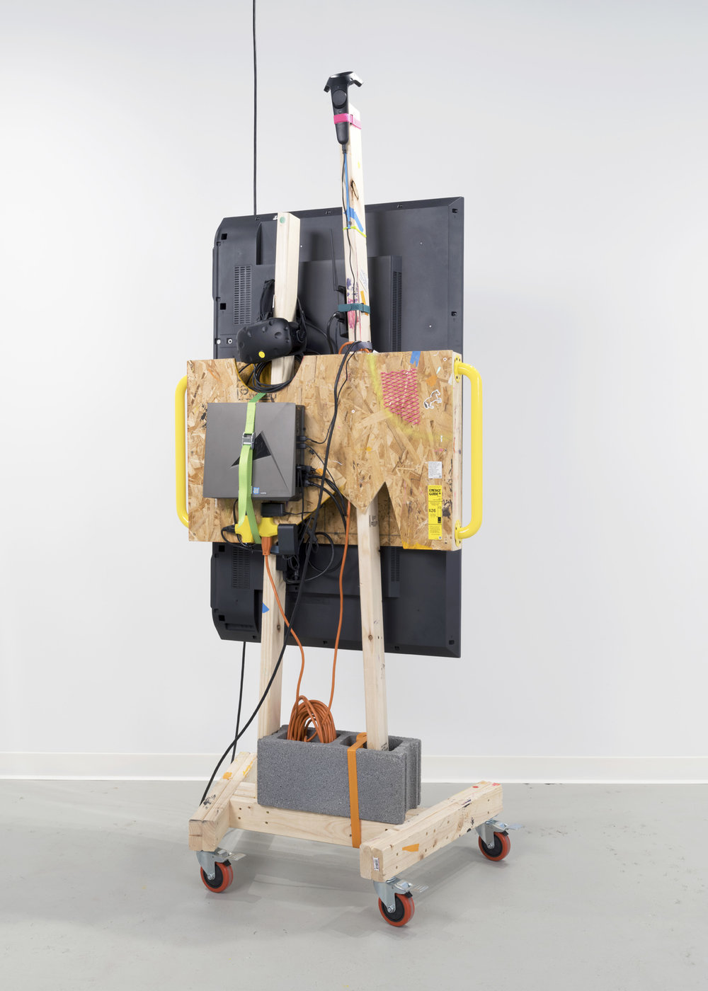 """Theo Triantafyllidis,  Studio Visit , 2018, 60"""" HD TV on wooden stand, room scale virtual reality system, gaming PC, wireless transmitter, concrete block"""