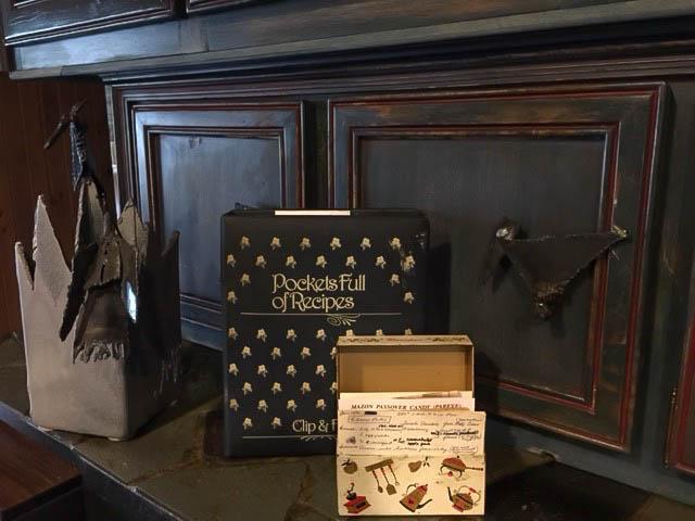Le classeur de recettes Braitstein et la boîte de recettes Steinberg s'installent sur le comptoir de la cuisine entre une sculpture de Braitstein et une poignée de porte d'armoire.