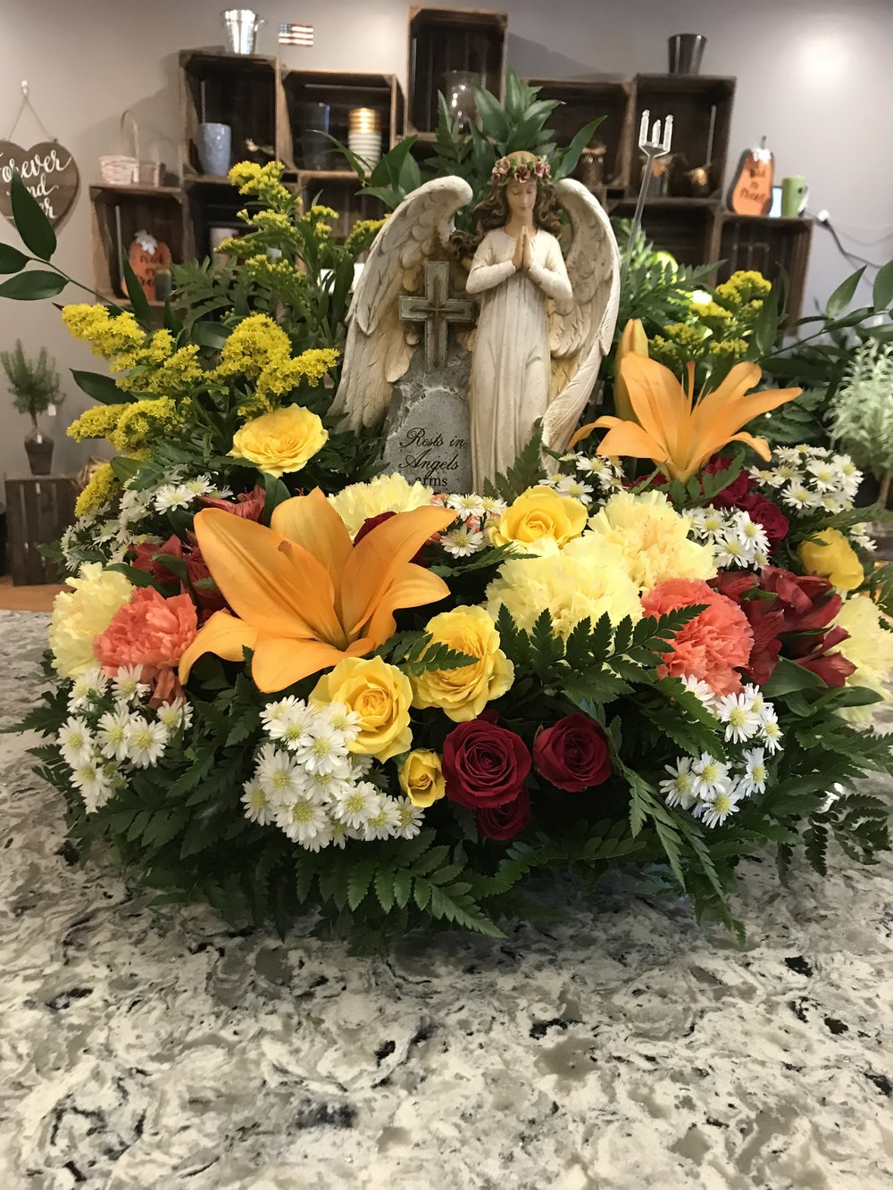 Angel Tribute - $150.00Orange Asiatic Lily, Yellow Spray Rose, Red Spray Rose, Yellow and Orange Carnation, White Monet Casino, Solidago.