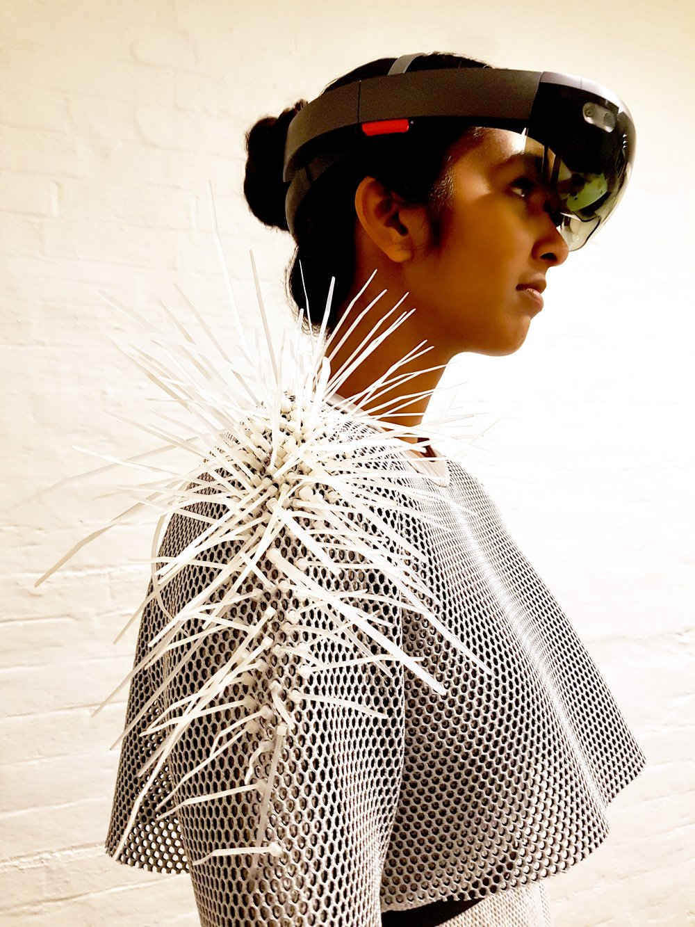 'Mycelium'    Zoe Mahony/Warren Armstrong  -  sARTorial 2017   Wearable technology: Could this be a way of communicating environmental data and sites of distress to a broader audience?   HoloLens, EL wire, arduino, polyester, batteries, computer, large AV screen   Model - Monisha Sami